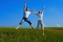 couple jumping in field